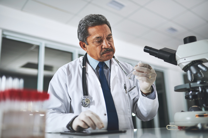 Male doctor examining the content inside a test tube next to his microscope